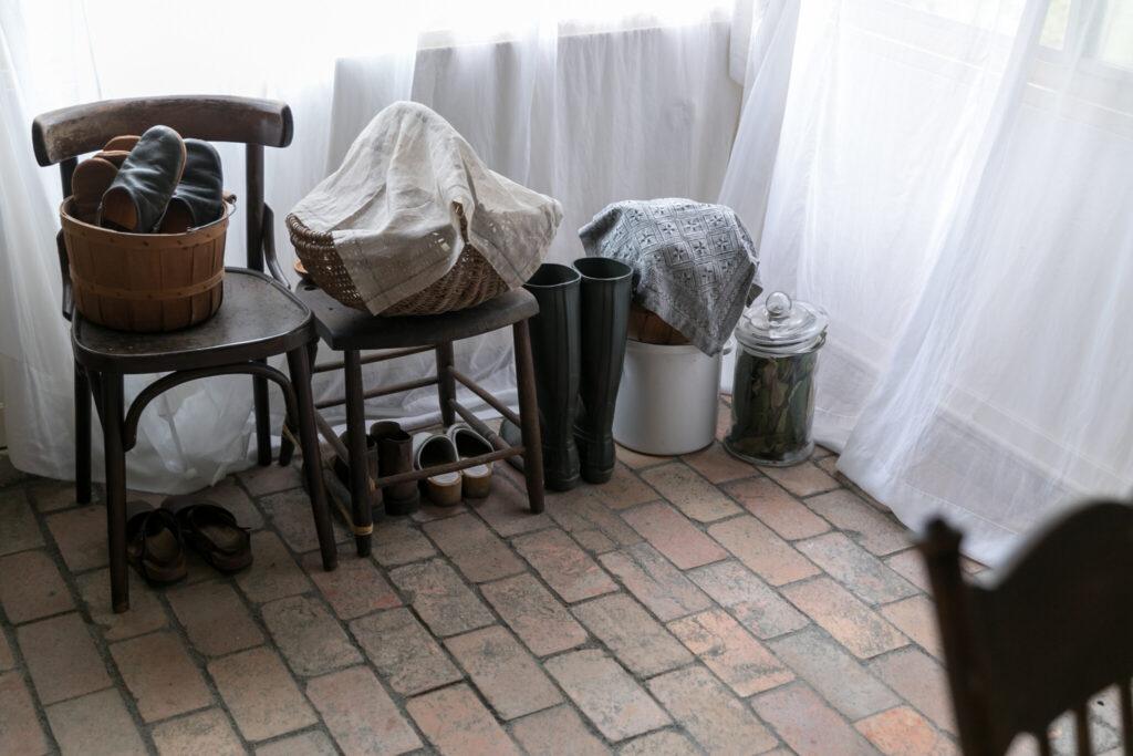 古い耐火レンガの土間と、白く柔らかなコットンオーガンジーのカーテンの組み合わせが美しい。右のビンの中は庭で採った枇杷の葉。