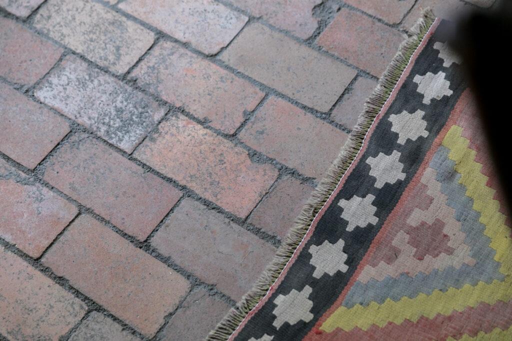 粉のセメントの上にレンガを並べてから水を巻く方法で作った土間。ラグは30年ほど使っている愛用品。