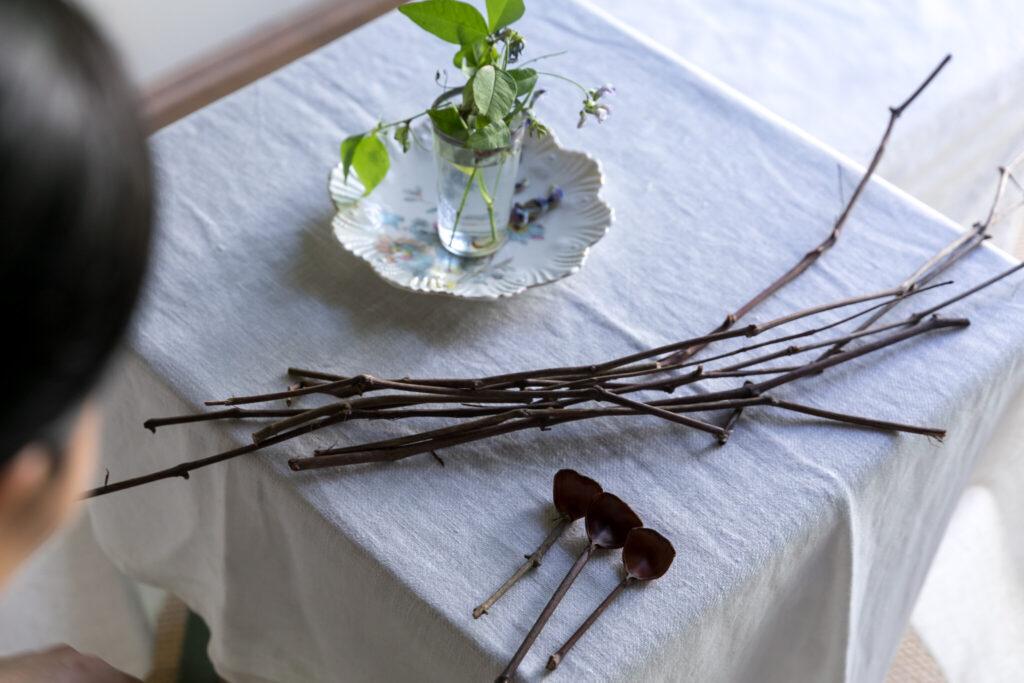柄は剪定したブドウの蔓。秋の手仕事を楽しむ山下さん。お花を生けたカップに花柄のお皿を敷いて。